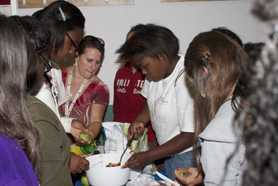 Pam Ingram, nutrition program associate with the University of Missouri Extension Service (center, in red), directs a group of campers at the UMSL Girls' Leadership Camp as they prepare a fruit salsa as part of a healthy eating class.