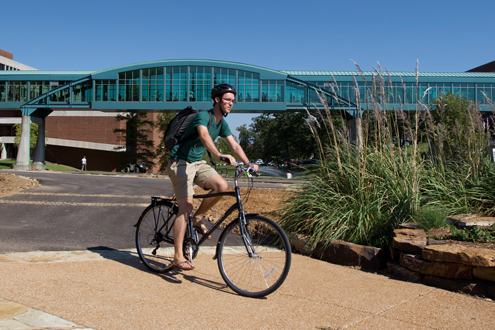 Ellis Anderson, an elementary education major at UMSL, rides the St. Vincent-Cross Campus Trail
