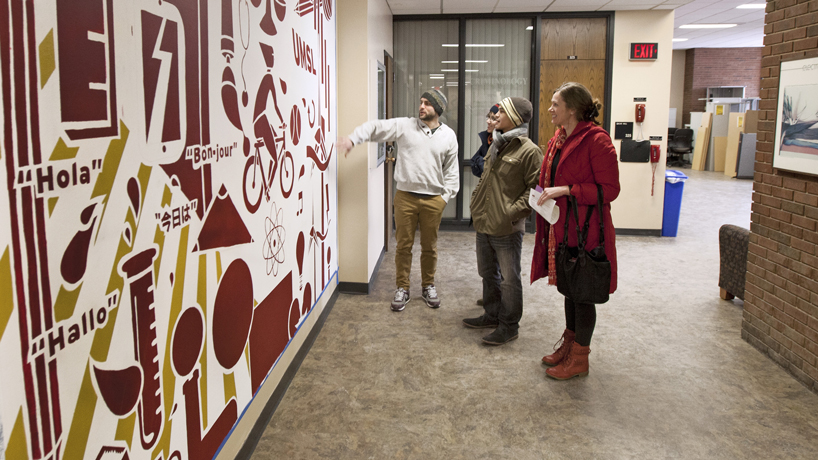 Visitors to the Lucas Hall foyer examine UMSL student Charlie Nowell's finished mural.