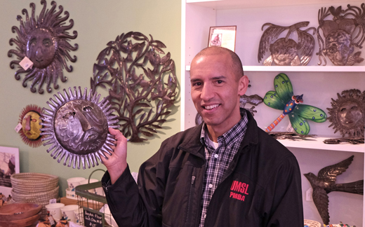 UMSL PMBA alumnus Julio Zegarra-Ballon poses with some of the fair trade merchandise in his story Zee Bee Market on South Grand Blvd. (Photo by August Jennewein)