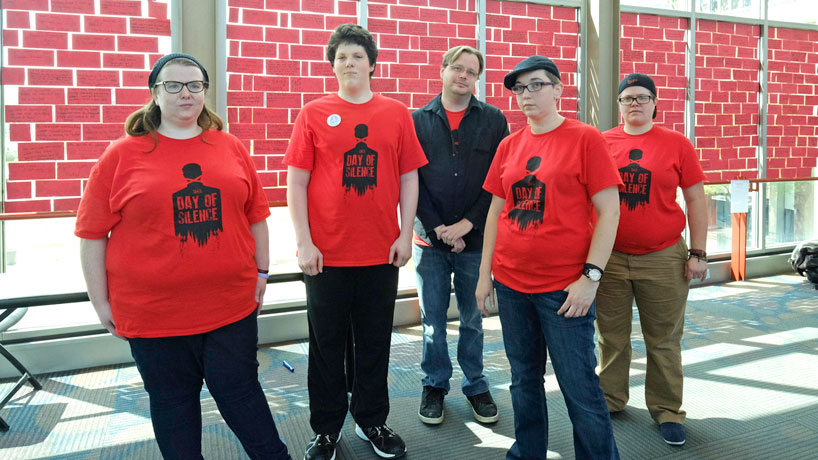 Junior liberal studies major Natalie Smith (in the hat) stands with fellow members of PRIZM, the queer-straight alliance at UMSL. As president of the student organization, she oversaw the Walls of Intolerance event, where students shared moments of discrimination on red paper bricks.