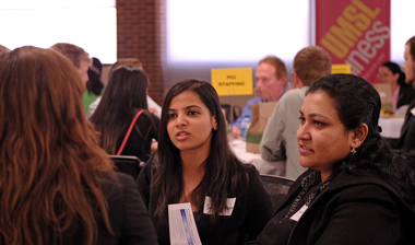 UMSL students Samyukta Varre and Gayathri Reddy talk with a recruiter from Panera Bread during the UMSL's Information Systems Career Conference. (Photo by August Jennewein)