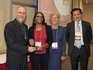 Sharon Johnson, professor of social work at UMSL, was named Senior Investigator of the Year. Johnson,  by the National Academy of Inventors. The recognition was announced during the annual Research & Innovation Week April 17-24 at UMSL. Pictured (from left) are Chancellor Tom George, Johnson, Director of the School of Social Work Lois Pierce and Vice Provost of Research Nasser Arshadi. (Photo by August Jennewein)