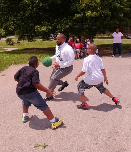 UMSL alumnus Howard Fields III, principal of Koch Elementary School in the Riverview Gardens School District, plays a friendly game of basketball with a few of his students during recess. (Photo by August Jennewein)