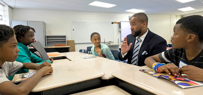 UMSL alumnus Howard Fields III, principal of Koch Elementary School in the Riverview Gardens School District, talks with students about a recent visit to St. Louis County Executive Steve Stenger's office . (Photo by August Jennewein)