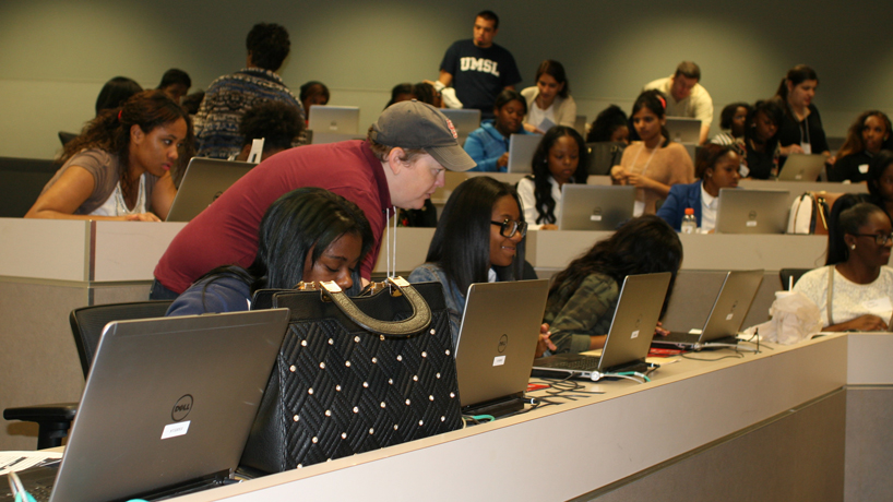 UMSL student Kat Mierek (baseball cap) helps Normandy High School students during a workshop on IBM's Bluemix software. (Photo by Jen Hatton)