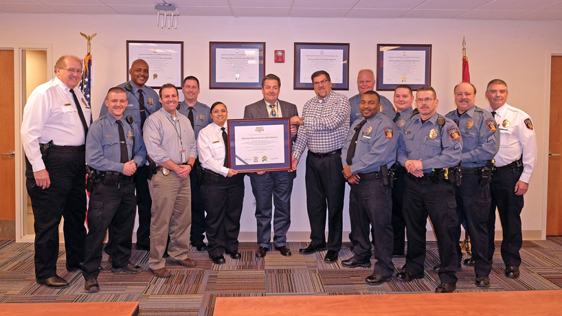UMSL's Police Department received re-accreditation    from the Commission on Accreditation for Law Enforcement Agencies, the gold standard in public safety standards. Pictured (from left) are: Captain Charles Roeseler, Officer Dustin Smith, Officer Cedric Carr, Det. Josh Shelton, Officer David Woods, Lieutenant Marisa Smith, Chief Forrest Van Ness, Paul Anderson, Officer Rich Jackubowicz, Officer Nigel Partee, Officer Brian Clements, Sergeant Tom McEwen, Sergeant Kevin Buchheit, Lieutenant Dan Freet  (Photo by August Jennewein)
