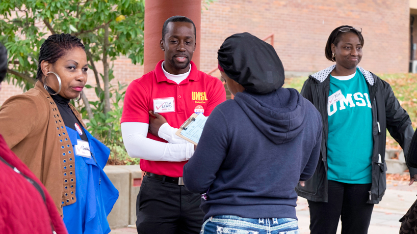 UMSL students Cynthia Davis, Tim Lewis and Kimberly Brown stand under and overhang and observe as a woman with a hat fills out a survey after voting.