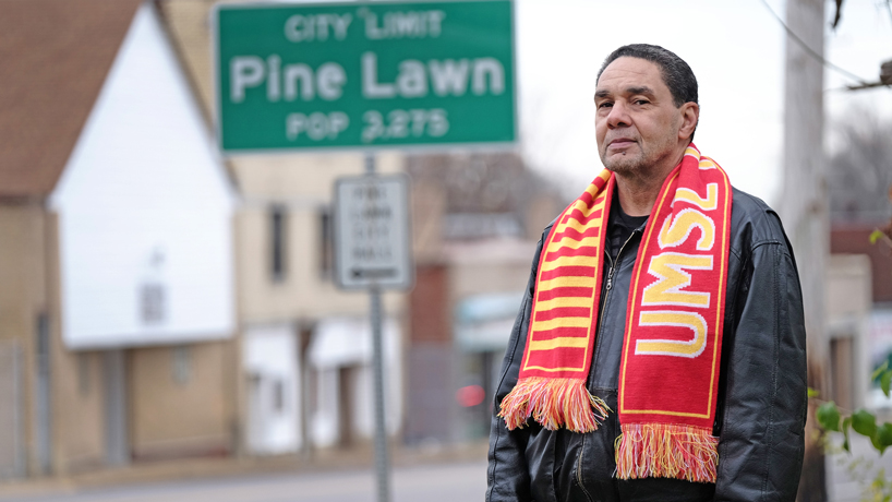 Elwyn Walls standing in front of the Pine Lawn city limit sign while wearing an UMSL scarf