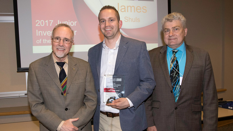 Chancellor Tom George (at left) and Interim Vice Provost for Graduate Studies and Research Chris Spilling (at right) present Assistant Professor of Educational Leadership and Policy Studies James Shuls with the 2017 Junior Investigator of the Year award at the reception concluding Research and Innovation Week on campus earlier this month. (Photo by August Jennewein)