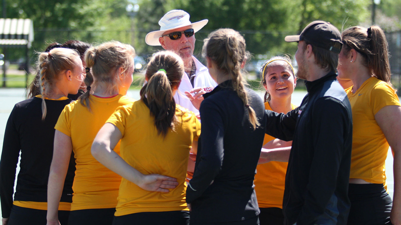 Coach Rick Gyllenborg surrounded by members of the UMSL women's tennis team