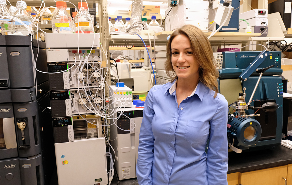 Lauren Jenkins, an Opportunity Scholar at UMSL and REU intern at the Danforth Center, poses in front of the mass spectrometer (the blue machine), which allows her to determine the composition of molecules and, although difficult because of their low levels in biological systems, quantify levels of acyl carrier proteins.