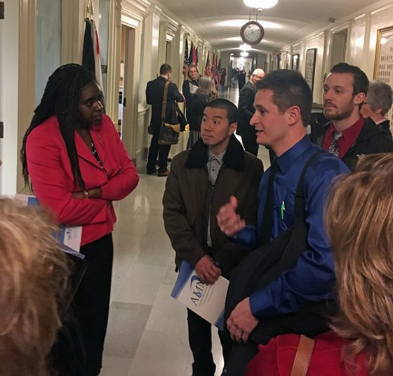 Robert Bohnert (right in blue) talks with Representative LaKeySha Bosley (left) about the shortage of primary care providers in Missouri and how nurse practitioners could help.