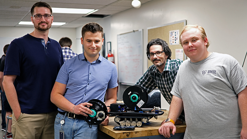 Mechanical engineering seniors Corey Milcic, Jonathan Olson and Kristian Stavri built a robot that lays extension cord during their capstone course. (Photos by Jessica Rogen)