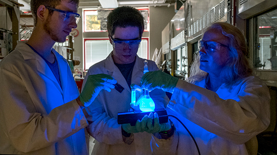 Janet Wilking demonstrates the fluorescent property of the germanium molecule she synthesize. The compounds can be used in OLEDs, known for lighting screens of electronic devices.
