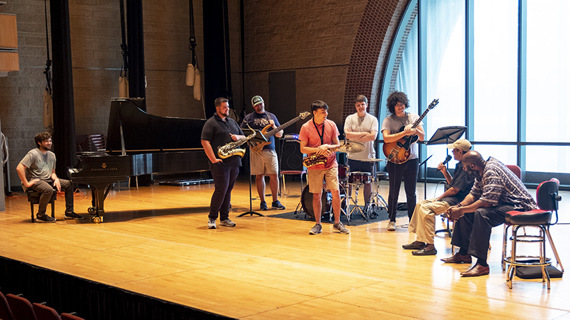 UMSL Jazz Combo members (from left) Ethan Saake, Trae Riley, Mike Owens, Nick Brothers, Dietrich Plyler and Nick Ayala as well as jazz pianist Sharp Radway (far right) listened to tales from behind the music from jazz legend Benny Golson. (Photos by August Jennewein)