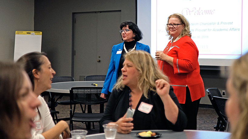 Professor of economics and Associate Provost for Academic Affairs Marie Mora (left) and Interim Chancellor and Provost Kristin Sobolik look on as the faculty brainstorm.
