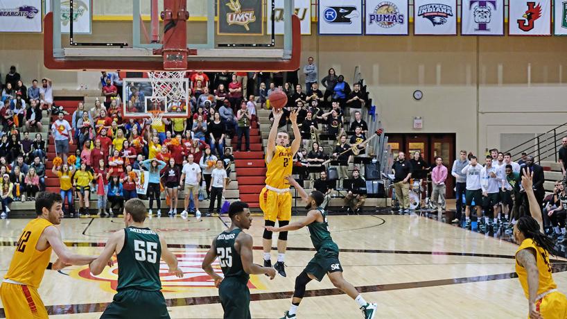 UMSL men's basketball player shoots three-pointer