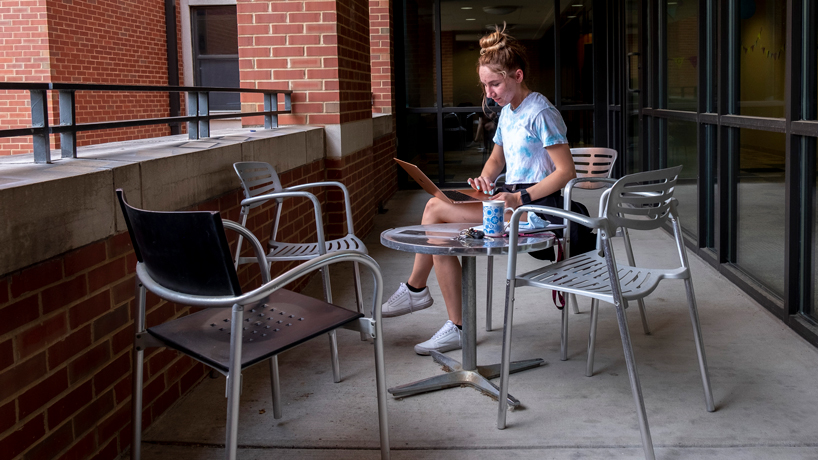 Rochelle Bruce uses her laptop on the balcony of Oak Hall