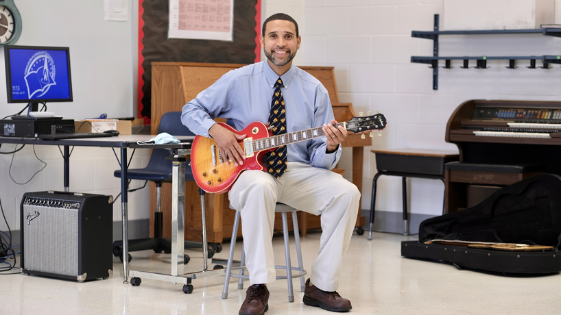 James Young sits with guitar in his classroom