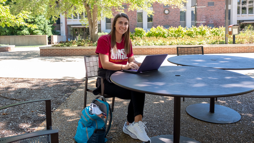 Charlotte Richards sitting with computer in the Quad