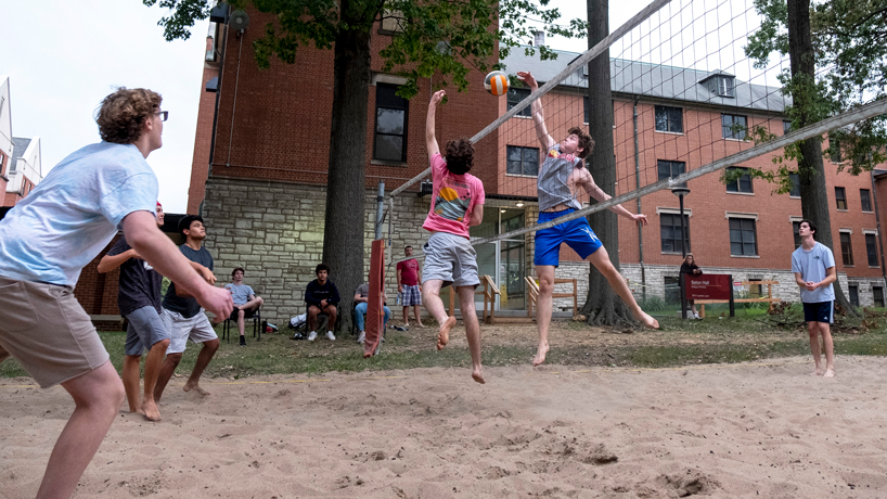 Students play sand volleyball on South Campus